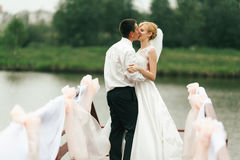 A wedding couple kisses tenderly standing on a bridge decorated Stock Images