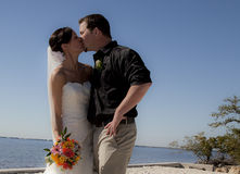 Wedding couple kissing on beach. A bride and groom kissing on a beach Stock Images