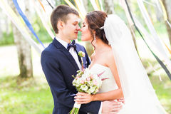 Wedding couple kissing,  bride holding a bouquet of flowers, groom embracing her Royalty Free Stock Photo