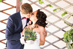 Wedding couple kissing, bride holding fan of peacock feathers, the groom embracing her Stock Photography