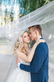 Wedding couple kissing covered veil .Wedding romantic couple is hugging each other. Beauty bride with groom stock photography