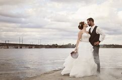 Bride and Groom standing on dock Royalty Free Stock Image