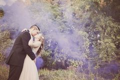 Bride and Groom kissing in forest with  purple smoke Royalty Free Stock Image