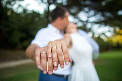 Wedding couple kissing with golden rings on their hands Royalty Free Stock Image