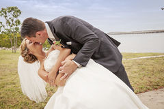 Wedding couple kissing. A groom dipping and kissing his bride by the water Stock Photo