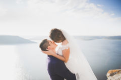 Wedding couple kissing and hugging on rocks near blue sea.  Royalty Free Stock Photo