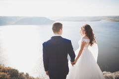 Wedding couple kissing and hugging on rocks near blue sea.  Stock Photos
