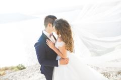 Wedding couple kissing and hugging on rocks near blue sea.  Royalty Free Stock Photography