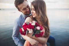 Wedding couple kissing and hugging on rocks near blue sea.  Stock Photos