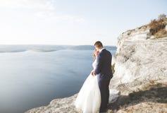 Wedding couple kissing and hugging on rocks near blue sea.  Royalty Free Stock Photos