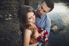 Wedding couple kissing and hugging on rocks near blue sea Royalty Free Stock Images