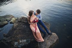 Wedding couple kissing and hugging on rocks near blue sea Royalty Free Stock Photo