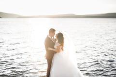 Wedding couple kissing and hugging on rocks near blue sea.  Stock Photo