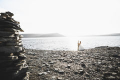 Wedding couple kissing and hugging on rocks near blue sea.  Royalty Free Stock Images