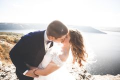 Wedding couple kissing and hugging on rocks near blue sea.  Stock Images