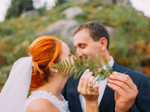Wedding couple kissing in mountains against the sky and covers faces by fern. Cute romantic moment. Stock Images
