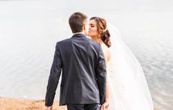 Wedding couple kissing near lake. Stock Photo