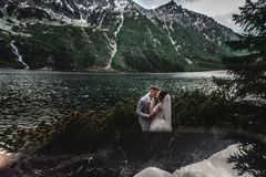 Wedding couple kissing near the lake in Tatra mountains in Poland. Morskie Oko. Beautiful summer day royalty free stock photo