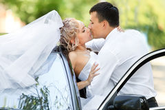Wedding couple kissing next to wedding car Royalty Free Stock Image