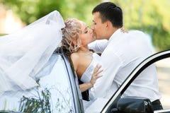 Wedding couple kissing next to wedding car Royalty Free Stock Image
