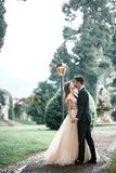 Wedding couple kissing in the park in the rain royalty free stock image