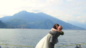Wedding couple kissing on the pier. Honeymoon in Como, Italy stock video footage