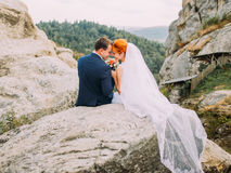 Wedding couple kissing at rocky mountains against the sky. Cute romantic moment. Royalty Free Stock Photography