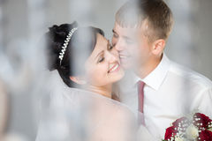 Wedding couple laughing and cuddling. Young joyful wedding Caucasian couple laughing and cuddling outdoors. Beautiful happy bride hugging and kissing with royalty free stock images