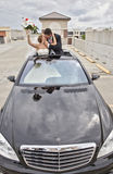 Wedding couple in Limousine sunroof. A kissing bride and groom excited out of sunroof in a limousine Stock Photography