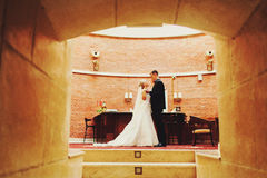 A wedding couple look at each other standing in the entrance stock photo