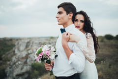 Wedding couple looking in mountain hill on sunset. Wedding couple in the evening. Peaceful romantic moment Stock Images