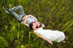 Wedding couple in love lying in green grass in summer meadow. Happy bride and groom relaxing outside Stock Photos