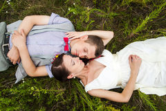 Wedding couple in love lying in green grass in summer meadow. Happy bride and groom relaxing outside Royalty Free Stock Image