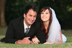 Wedding Couple Lying on Grass Royalty Free Stock Image