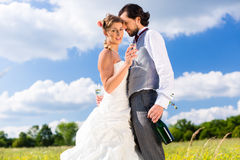 Wedding couple on meadow kissing Stock Images