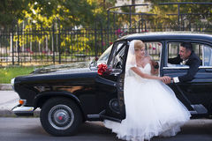 Wedding couple meet in a vintage car stock images
