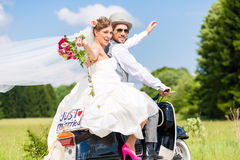Wedding couple on motor scooter just married. Wedding groom and bride driving motor scooter having fun, a just married sign attached stock photography