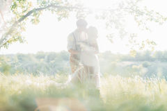 Wedding couple on  nature.  bride and groom hugging against the sun at wedding. Wedding couple on the nature. the bride and groom hugging against the sun at the Stock Photo
