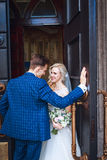 Wedding couple near a church. Wedding couple is hugging each other. Beauty bride with groom . stock image