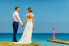 A wedding couple near the ocean. A happy wedding couple is holding their hands and looking at each other near the ocean and a pier stock photography