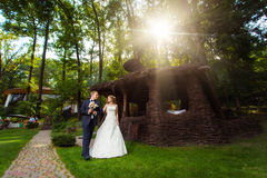 Wedding couple near summer house. Wedding couple near decorative summer house in sunlight Royalty Free Stock Photography
