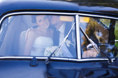 A wedding couple in old car Stock Images