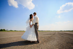 Wedding couple outdoor. Wedding couple are dancing on the field at midday sun Royalty Free Stock Image
