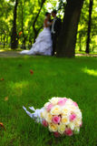 Wedding couple in the park. Focus on bouquet Royalty Free Stock Image