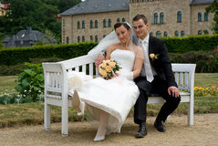 Wedding couple on park bench Royalty Free Stock Photography