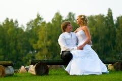 Wedding couple on park bench. Wedding couple sitting on wood park bench Stock Photo