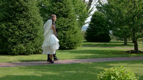 Wedding couple in a park. Bride and groom walking. Our path to happiness. Love and strive to unity stock video footage