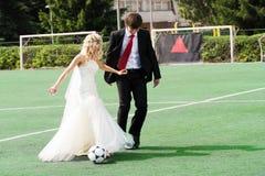 Wedding couple playing football Stock Image