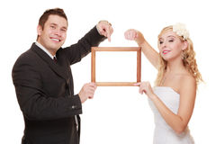 Wedding couple pointing empty frame for photo. Royalty Free Stock Photos