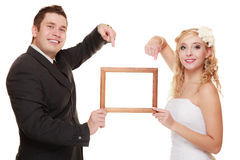 Wedding couple pointing empty frame for photo. Stock Photography